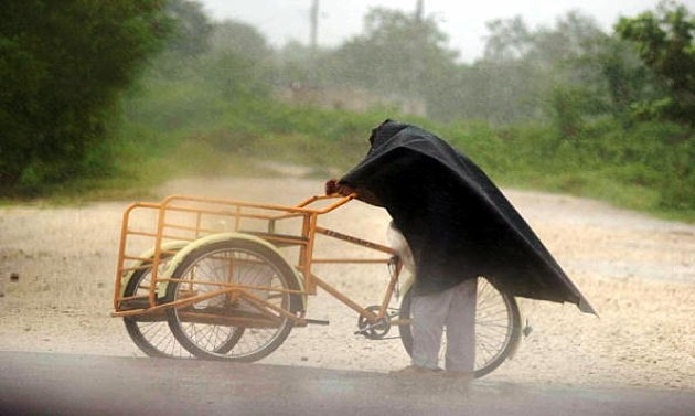 A street vendor tries to walk against the strong winds, he's struggling to ride his bike into the wind
