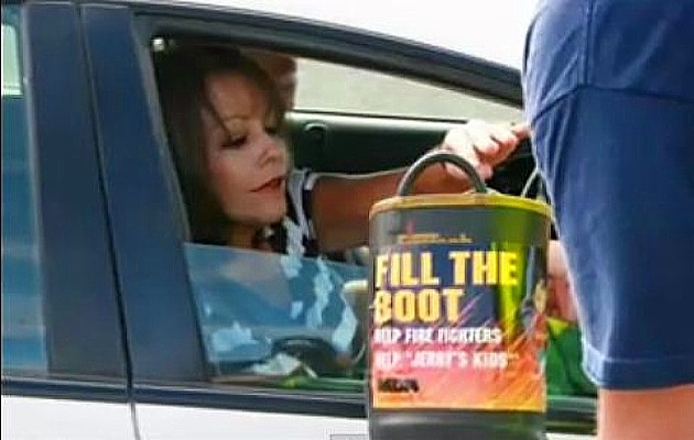 A lady is donating money to 'Fill the Boot' campaign for MDA