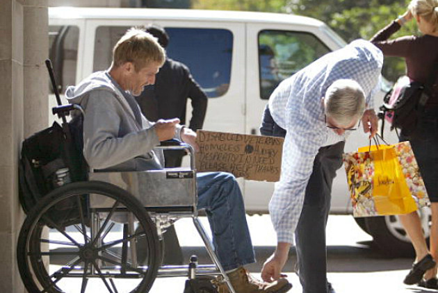 a panhandler receives money from a passerby