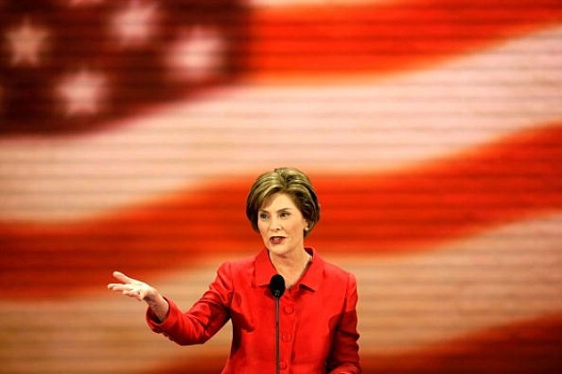 Former First Lady Laura Bush Speaking in front of big flag