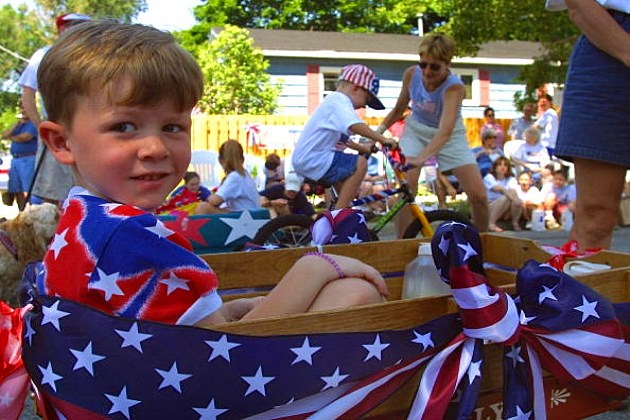 A boy rides in his Radio Flyer wagon as his parents march in the Independence Day parade