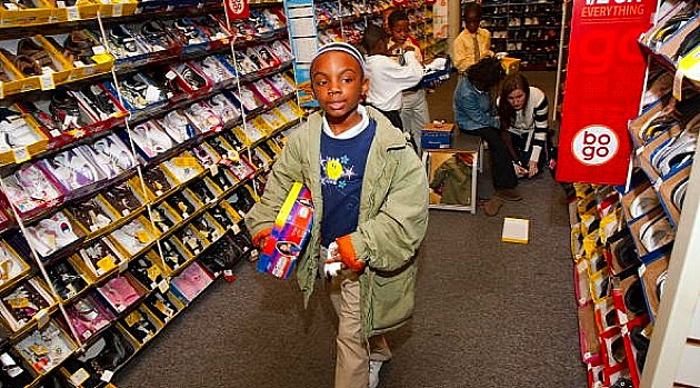 Children pick out their free shoes and try them on inside the store at Payless Shoe Source