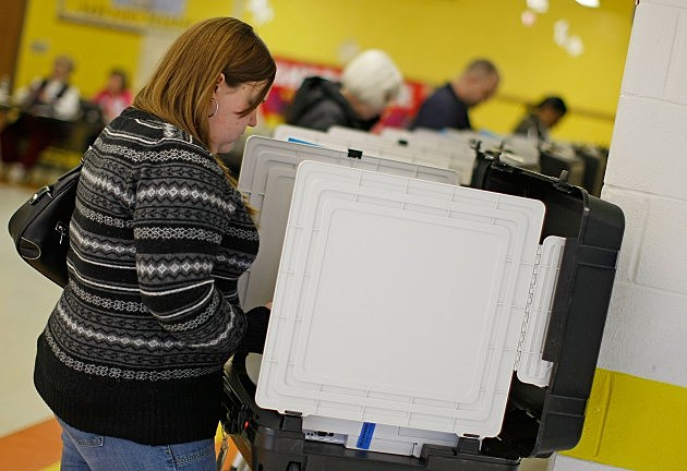 Voter Lauren Walker stands at a voting booth to cast her ballot