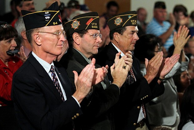 U.S. veterans, (L-R) Jim Hopper of the Army, Steve Hunt of the Navy, and Ronald Kirby of the Marine Corps, applaud