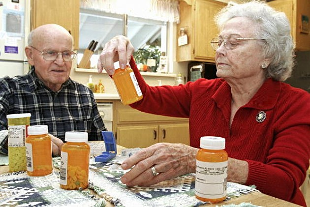Toby Anderson, 82, watches as his wife Amy, 83, divides his eight prescription drugs into a weekly schedule at their home