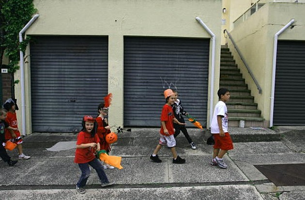 Children walk though the streets as they trick or treat homes on Halloween Day