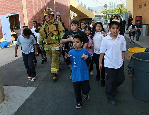 Students practice fire safety evacuation with Firefighters