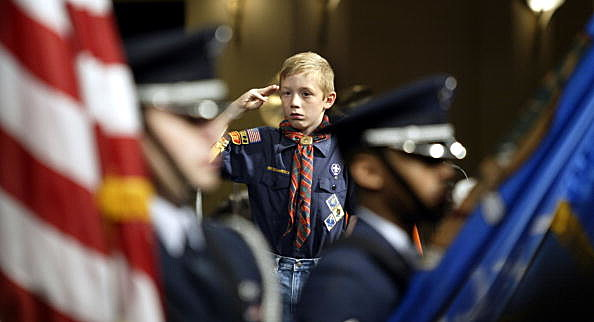 A Cub Scout salutes the honor guard