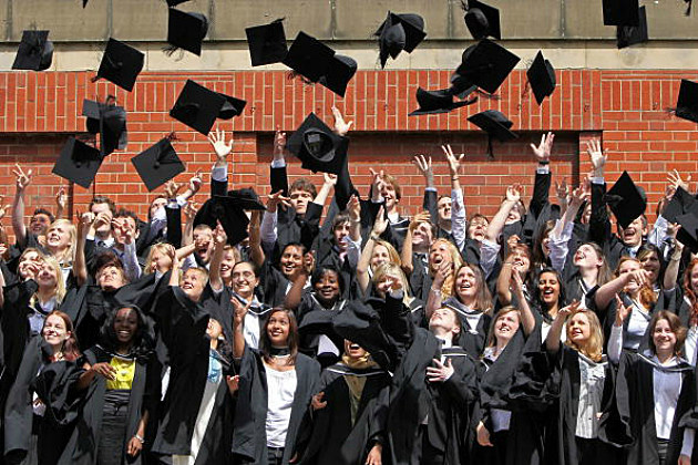 Students throw their mortarboards in the air during their graduation