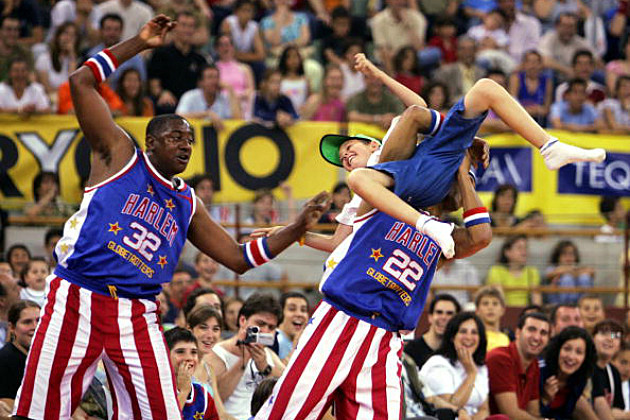 2 Globetrotters carry a kid on to the court